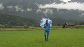 A young woman walking in countryside under the rain. A young woman walking on green grass with umbrella under the rain stock footage
