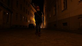 Young woman is walking through dark streets of old town in Europe. Riga, Latvia stock video footage
