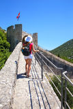 Young woman walking on the defensive wall of Ston town, Peljesac Royalty Free Stock Images