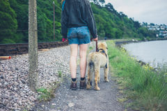 Young woman walking dog by railroad tracks Royalty Free Stock Photos