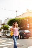 Young woman walking down a brightly lit street. Young woman of caucasian ethnicity walking down a brightly lit street Stock Image