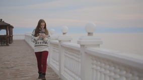 The young woman is walking down the quay with white old fashioned fence made of stone and with the tablet pc in her stock footage
