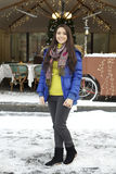 Young woman walking down snow covered street Royalty Free Stock Photography