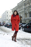 Young woman walking down snow covered street Stock Photo