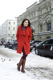 Young woman walking down snow covered street Royalty Free Stock Image