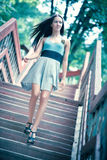 Young woman walking downstairs. Soft blue tint Royalty Free Stock Photography