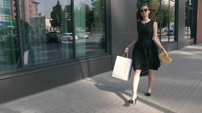 Young woman walking downtown and looking at her purchases stock footage