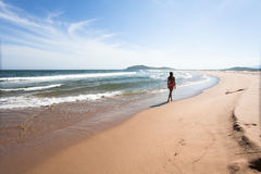 Young woman walking through the empty, wild beach against a blue sky, yellow sand and sea. Wide angle. Royalty Free Stock Photos