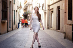 Young woman walking on the Europe street in white dress Stock Images