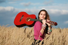 Young woman walking on field and carrying a guitar Royalty Free Stock Photos