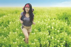 Young woman walking in the field flower. Young woman carrying a backpack while walking in the field flower to trek a mountain Stock Image