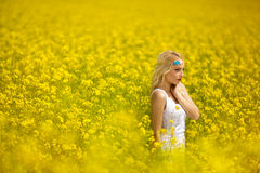 Young woman walking through a field of flowers Stock Image