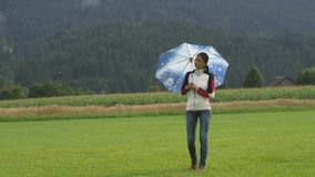 A young woman walking on the field holding umbrella. A young woman walking on grass holding umbrella and looking at the sky and waiting when the rain stops stock footage