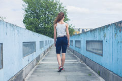Young woman walking on a foot bridge Stock Images