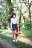 Young woman walking in the forest and playing guitar, summer nature, bright sunlight, shadows and green leaves, romantic feelings stock photography