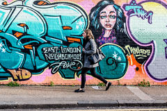 Young woman walking in front of a wall with graffiti Stock Image