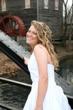 Young woman walking in front of a water wheel Stock Photography