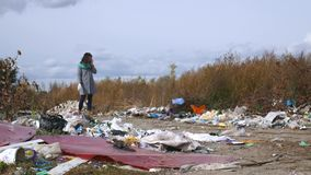 Young woman walking through a garbage dump.  stock footage