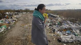 Young woman walking through a garbage dump.  stock video