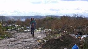 Young woman walking through a garbage dump Royalty Free Stock Image