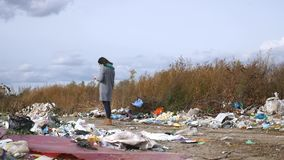 Young woman walking through a garbage dump.  stock video footage