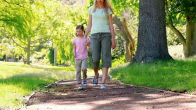 Young woman walking with a girl. In a park stock video footage