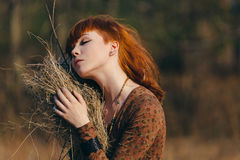 Young woman walking in golden dried grass field Stock Photography