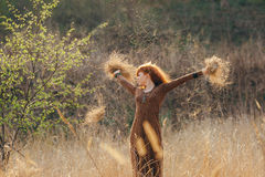 Young woman walking in golden dried grass field royalty free stock photography