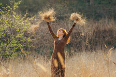 Young woman walking in golden dried grass field Royalty Free Stock Photo