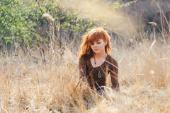 Young woman walking in golden dried grass field Stock Image