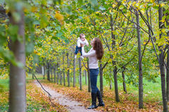 Young woman walking with her baby in a park. Young beautiful women walking with her baby in a park Royalty Free Stock Images