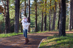 Young woman walking with her baby in a park Royalty Free Stock Photography