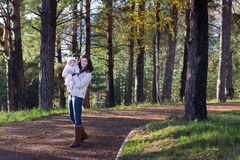 Young woman walking with her baby in a park Royalty Free Stock Photos