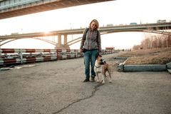 Young woman is walking with her dog in the evening park. Royalty Free Stock Images
