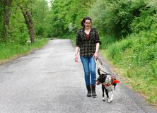 Young Woman Walking her dog for exercise. Young woman walking her mixed breed dog on a rural road Royalty Free Stock Image