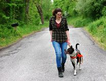 Young Woman Walking her dog for exercise. Young woman walking her mixed breed dog on a rural road Royalty Free Stock Photos