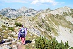 Young Woman Walking on High Mountain Ridge Royalty Free Stock Photo
