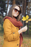 Young woman walking holding autumn leaves in park Royalty Free Stock Image