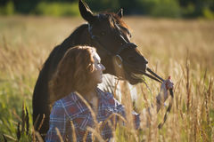 Young woman walking with the horse in meadow at summer day Royalty Free Stock Image
