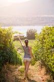 Young woman walking inbetween rows of grapes growing on an Okanagan vineyard. royalty free stock photography