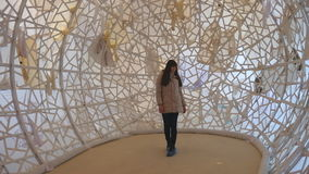 Young woman walking inside of contemporary art object at museum. Girl examining modern art