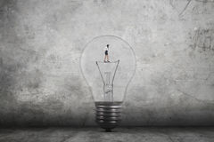 Young woman walking inside light bulb Royalty Free Stock Photos