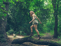 Young woman walking on log in forest Stock Image