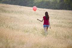 A young woman walking through long grass holding a red balloon Royalty Free Stock Images
