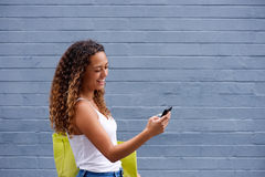 Young woman walking and looking at mobile phone Royalty Free Stock Photos