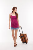 Young woman walking with luggage. Royalty Free Stock Image