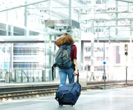 Young woman walking with luggage. On train station platform Stock Photo
