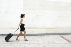 Young Woman Walking with Luggage on Wall Background. stock image