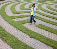 Young Woman Walking Through Maze with Cellphone Stock Photo