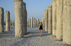 Young woman walking in a middle of concrete pilings Royalty Free Stock Photos